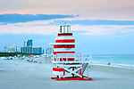 Red and white lifeguard stand designed to look like a lighthouse at the South Beach jetty on Miami Beach, Florida.