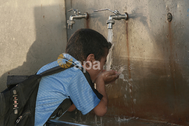A Palestinian boy drinks water from a public tap in Rafah refugee camp in southern Gaza Strip, Oct. 30, 2013. The United Nations Relief and Works Agency for Palestine Refugees (UNRWA) has removed food aid for 9,558 families in Gaza since the beginning of the year, while adding only 5,430 new families to the programme. Photo by Eyad Al Baba