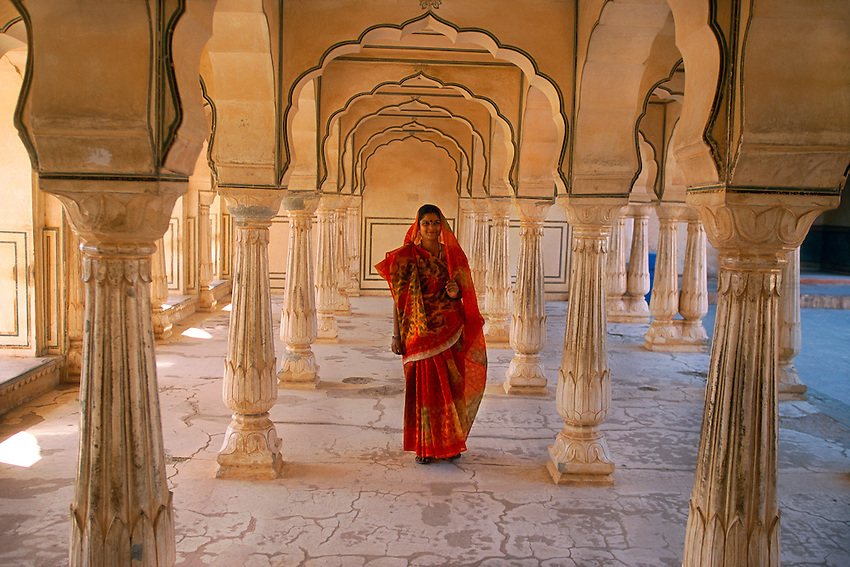 Indian woman walking thru arches at the Amber Fort and Palace near Jaipur, Rajasthan, India