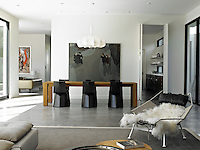 Looking from the living to the dining area with a long wooden dining table and futuristic black metal dining chairs