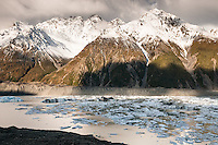 Tasman Glacier terminal lake with icebergs and ice debris after massive terminal face calving in 2010 under warm evening light, Aoraki Mt. Cook National Park, Mackenzie Country, UNESCO World Heritrage Area, New Zealand, NZ