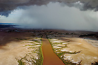 Aerial of tidal mud flats just outside town of Wyndham.  This scene is about one minute away from the landing strip. We circled in front of this single cell storm as it moved across the landscape.  Aerials are the King River, and many snaking rivers/creeks that flow to the Cambridge Gulf. <br />  Mudflats are drivable during the dry season.  This is mpossible to do during the wet... The rains wash the dirt into the rivers and creeks and the silt runs out to the ocean.