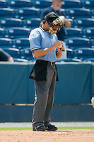 Home plate umpire Aaron Roberts checks the baseball during a South Atlantic League game between the Greenville Drive and the Rome Braves at State Mutual Stadium July 25, 2010, in Rome, Georgia.  Photo by Brian Westerholt / Four Seam Images
