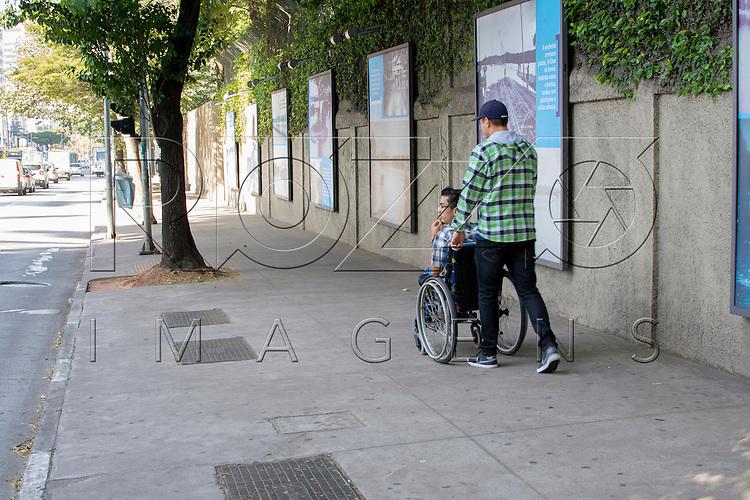Cadeirante passeando em calçada com passagem livre e plana na Avenida Faria Lima, São Paulo - SP, 07/2016.