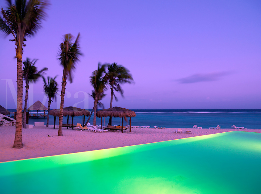 Mexico Quintana Roo Yucatan Peninsula Akumal Mayan Riviera,infinity pool illuminated by the edge of a beach with the sea in the background