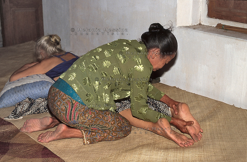 Indonesia, Java island: a  &quot;duk&ugrave;n&quot; applies the natural javanese massages using herbal oil.<br />