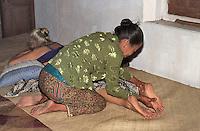Indonesia, Java island: a  &quot;duk&ugrave;n&quot; applies the natural javanese massages using herbal oil.<br /> Indonesia; Giava, una duk&ugrave;n usa le tecniche del massaggio tradiazionale giavanese con olio a base di erbe.