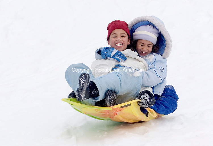 WATERBURY, CT - 16 DECEMBER 2007 - 121607JW05.jpg -- Friends Emiliane Cruz age 7 and Joshlynn Pena age 10 take a ride together while sliding down a hill a Fulton Park in Waterbury Sunday afternoon. Jonathan Wilcox Republican-American