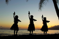 Three hula dancers at sunset at Olowalu, Maui.