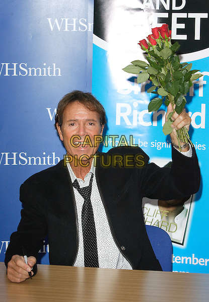 "SIR CLIFF RICHARD .Sir Cliff Richard at a signing of his new autobiography ""My Life, My Way"" at Lakeside Shopping Centre, Thurrock, London, England, September 5th 2008..half length bunch of red roses flowers sitting black jacket tie suit.CAP/ROS.©Steve Ross/Capital Pictures"