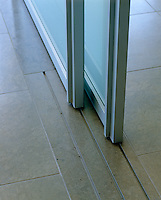 The glass doors run along tracks carved into the stone floor ensuring the continuity of the flooring on both sides