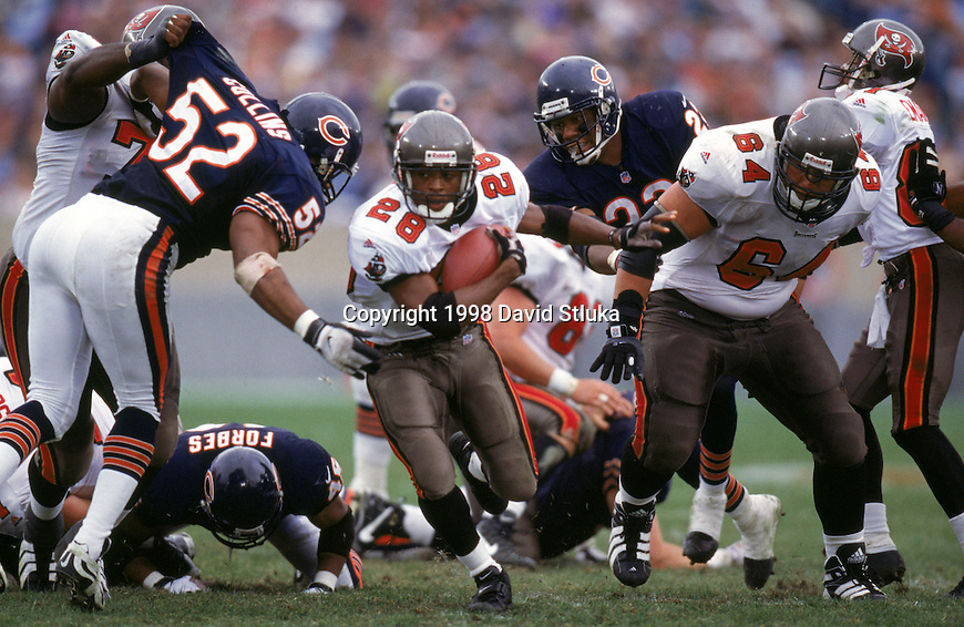Tampa Bay Buccaneers running back Warrick Dunn (28) carries the ball during an NFL football game against the Chicago Bears at Soldier Field on November 29, 1998 in Chicago, Illinois.  The Bucs won 31-17. (Photo by David Stluka)