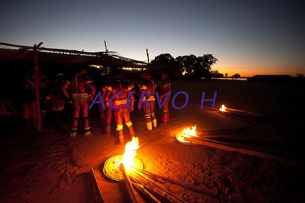 """Cerimônia do Kwarup na aldeia Kamaiurá, no Parque indígena Xingu.<br /> <br /> O Kwarup (nome do ritual na língua kamaiurá) é considerado o grande emblema do Alto Xingu e trata-se de uma cerimônia funerária, que envolve mitos de criação da humanidade, a classificação hierárquica nos grupos, a iniciação das jovens e as relações entre as aldeias. Ao longo dos meses que se seguem até o encerramento ocorrem, não necessariamente todos os dias, dois tipos de danças e o toque de longas flautas (uruá, na língua dos Kamaiurá), sempre retribuídos com oferecimento de alimentos pelos """"donos"""" do Kwarup. O foco de orientação dessas atividades rituais é sempre a cerca sobre a sepultura. No pátio da aldeia promotora do rito, cada falecido homenageado é representado por uma seção de tronco de cerca de dois metros. São de uma espécie vegetal que tem distintas denominações conforme as diferentes línguas xinguanas. Os Kamaiurá a chamam de Kwarup, a mesma madeira com que o herói mítico fez as mulheres que enviou para se casarem com o jaguar. Os troncos são colocados um ao lado do outro, de pé, embutidos em buracos de 50 cm de fundo. São pintados e ornamentados com adornos plumários e cintos masculinos. A única distinção entre os troncos que representam homens e os que representam mulheres é que os primeiros são guarnecidos com mechas de algodão não fiado. Também os homens comuns falecidos têm direito a ser representados por troncos, porém menos grossos e com ornamentação mais simples. Os espíritos dos mortos homenageados ficam junto aos troncos na última noite do rito e a isto se reduz a sua participação. Ao anoitecer, acendem-se fogueiras diante de cada tronco do Kwarup. Enquanto os moradores da aldeia anfitriã se revezam, velando os troncos e chorando os falecidos homenageados, os visitantes, cada acampamento por sua vez, entram na aldeia trazendo achas de pindaíba para remanejar as fogueiras, numa cena movimentada e tensa. Fonte: ISA<br /> Querência, Mato Grosso, Brasil.<br />  25 e """