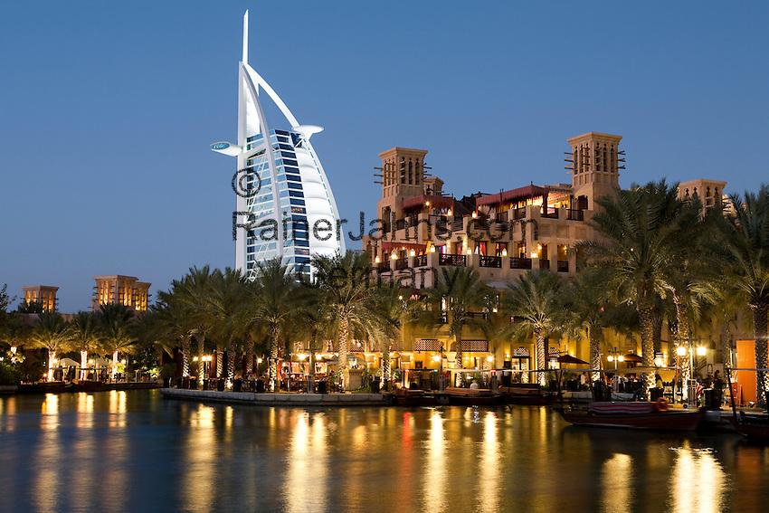 United Arab Emirates, Dubai: Restaurants in Madinat Jumeriah with Mina A'Salam Hotel and Burj Al Arab at night