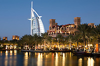 United Arab Emirates, Dubai: Restaurants in Madinat Jumeriah with Mina A'Salam Hotel and Burj Al Arab at night