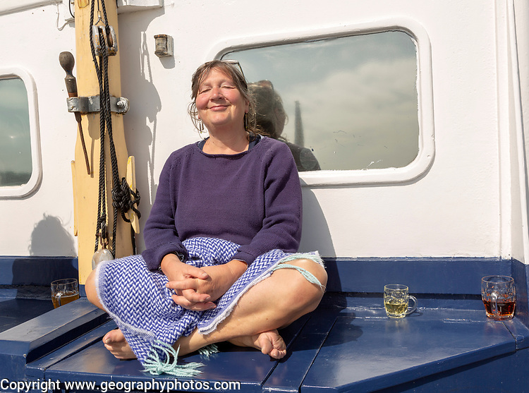 Lady Florence boat trip cruise River Ore, Orford Ness, Suffolk, England woman sitting in sun with drink onboard Model Released