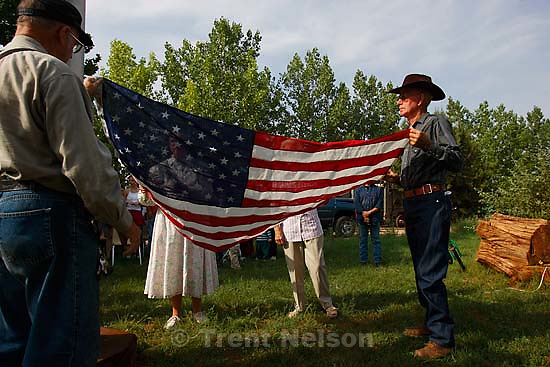 Flag raising by seven survivors of 1953 raid. Dedication and unveiling of monument dedicated to the Short Creek polygamy raid of 1953, in Cottonwood Park, put into motion by Winston Blackmore.<br />