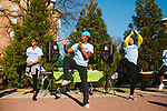 A.J. Johnson (center), a Spelman alum and fitness trainer, leads a crowd in a stretch and warm-up before the first annual Wellness Revolution 5K Run and Walk on the Spelman College campus in Atlanta, Georgia April 6, 2013.