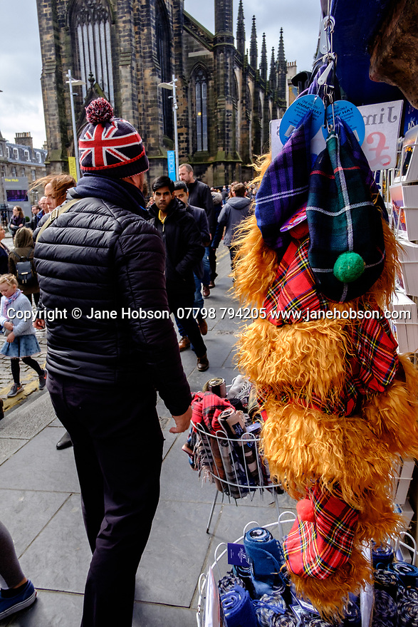 "Edinburgh, UK. 15.04.2017. A man in a Union Flag decorated wolly hat passes a shop selling ginger ""Jimmy"" hats, on the Royal Mile. Photograph © Jane Hobson."