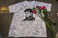 NEW YORK APRIL 21: Flowers lay on a T-shirt signed by fans of singer Prince at a makeshift memorial place created outside Apollo Theatre in Harlem, New York City, Friday, April 21, 2016. The pop star died at the age of 57.Photo by VIEWpress/Maite H. Mateo