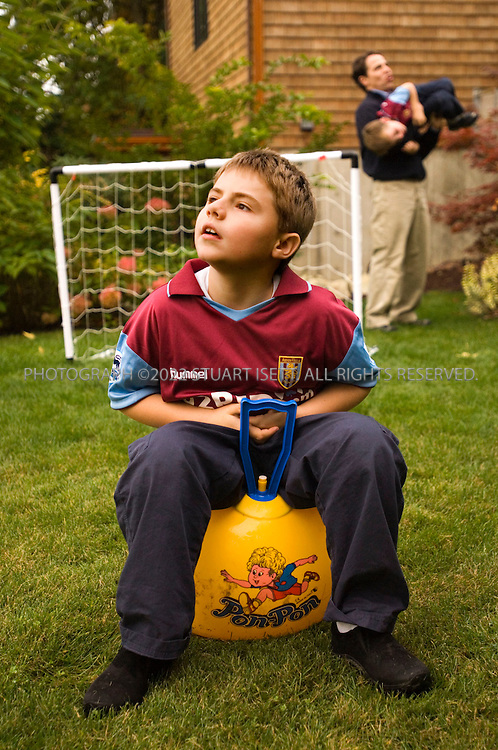 10/24/2006--Seattle, WA, USA..8 year old Clark Perry (left) plays with his father, David Perry, and younger brother Owen (4) in the family's garden in Seattle. Clark was diagnosed with autism when he was 3 1/2 years old...Photograph By Stuart Isett.All photographs ©2006 Stuart Isett.All rights reserved.