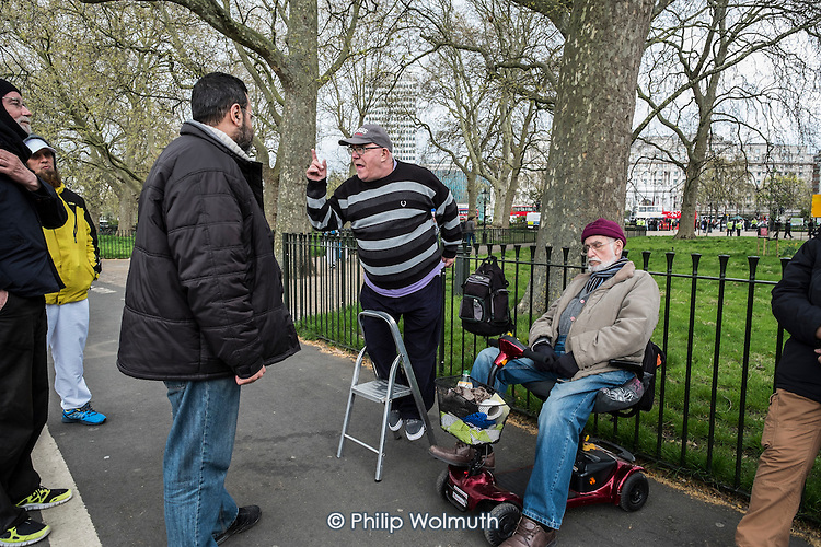 Christian preacher and man on a mobility scooter, Speakers' Corner, Hyde Park, London.