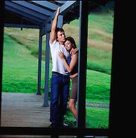 Couple standing on porch embracing seen through screen door