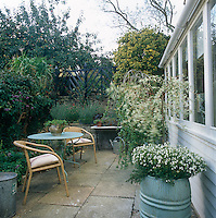 A paved patio area outside a conservatory with two wicker chairs and a painted metal table. A trellis fence atop a stone wall and shrubs are placed around the boundary keep the garden private.