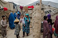 KABUL, AFGHANISTAN - OCTOBER 13: Afghan women and children depart an outreach therapeutic feeding program centre at an informal settlement in Kabul. Aid workers working for Action contre la Faim (ACF), a French NGO, provide care and supplies for malnourished children at an outreach program at a Kabul Informal settlement, housing internally displaced persons.