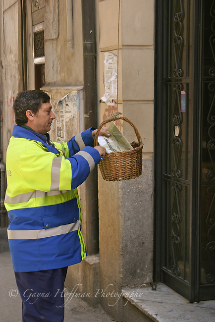 Sicilian post man delivering mail in pull up basket. Italy
