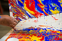 Donna McDonald manipulates wet primary colors on canvases to form the background for her next painting during Professor Tom Chung's Intermediate Painting (ART A313) class in UAA's Fine Arts Building.