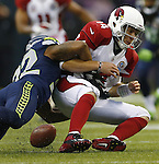Arizona Cardinals quarterback Ryan Lindley fumbles the ball while being sacked by Seattle Seahawks strong safety Jeron Johnson at CenturyLink Field in Seattle, Washington on  December 9, 2012.  The Seahawks beat the Cardinals 58-0.  ©2012. Jim Bryant Photo. All Rights Reserved.