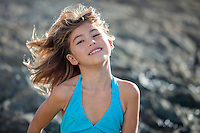 A young girl enjoys the wind at a rocky North Shore beach on O'ahu.