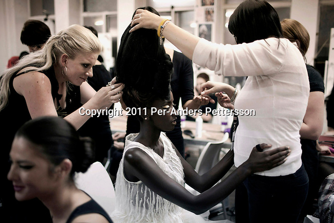 JOHANNESBURG, SOUTH AFRICA - FEBRUARY 19: Huguette Marara a model from Rwanda, is fitted with a hair piece before a show with the designer David Tlale, at his studios at the Joburg Fashion Week on February 19 2011, in Johannesburg, South Africa. David Tlale, is an award winning designer and one of South Africa's finest designers, dressing celebrities and others in couture with elegance and high quality material. He held his show at the Mandela Bridge in downtown Johannesburg. A logistical nightmare, the bridge was closed and turned into a  catwalk at midnight with hundreds of people watching the show.  92 models, one for each of Nelson Mandela's years walked the 285 meter bridge, maybe the longest catwalk in the world. South African top designers with showed their 2011 Autumn & Winter collections during the 5 day event. (Photo by Per-Anders Pettersson)