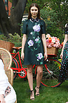 "Model poses in a hunter green and lilac floral placement printed silk dress, with lace and organza double collar, from the Lela Rose Resort 2018 ""Garden Party"" collection in Jefferson Market Garden on June 7 2017, during Resort Fashion Week in New York City."