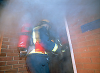 Firefighter in breathing apparatus going through the front door of a house on fire. This image may only be used to portray the subject in a positive manner..©shoutpictures.com..john@shoutpictures.com