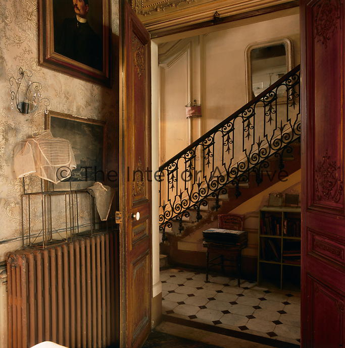 A view through a pair of carved wood doors to an entrance hallway with a grand marble staircase beyond.