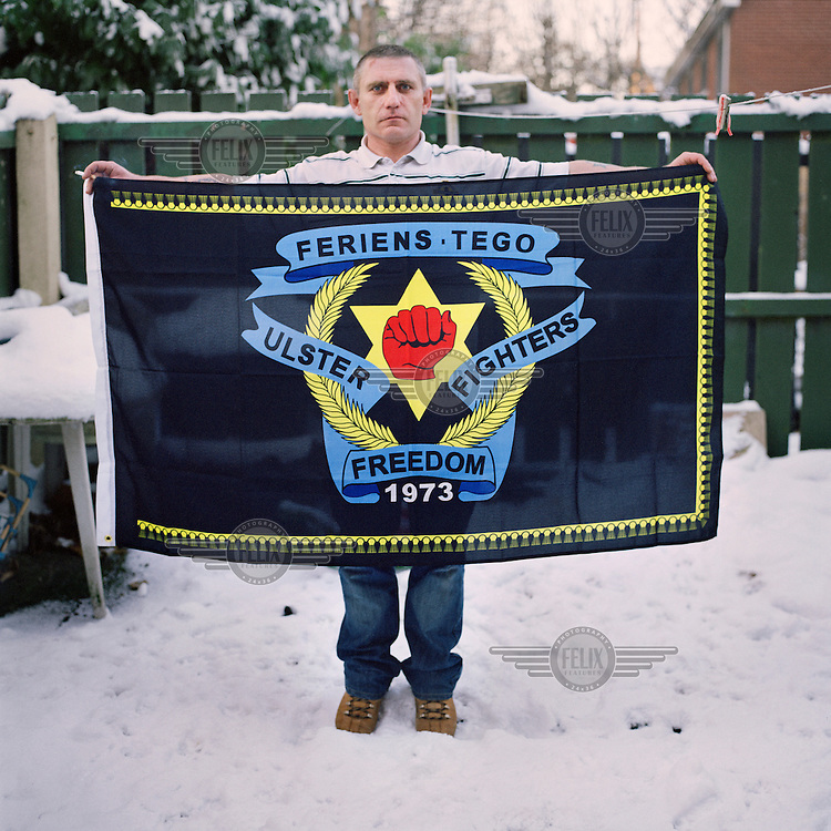 Graeme holding an Ulster Freedom Fighters (UFF) flag in Belfast. The flags were banned as part of the Good Friday Agreement since they are a sign of open support for a terrorist organisation.