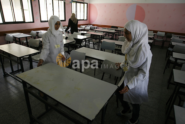 Palestinian school girls wait at their a closed school during a strike of the employees of former Palestinian government in Gaza Strip to demand for pay their salaries, in Rafah in the southern Gaza strip, on Oct. 15, 2014. Photo by Abed Rahim Khatib