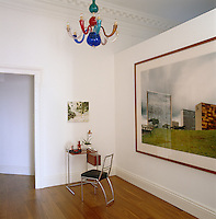 A small work table and chair on a landing dominated by a contemporary photograph of a cityscape