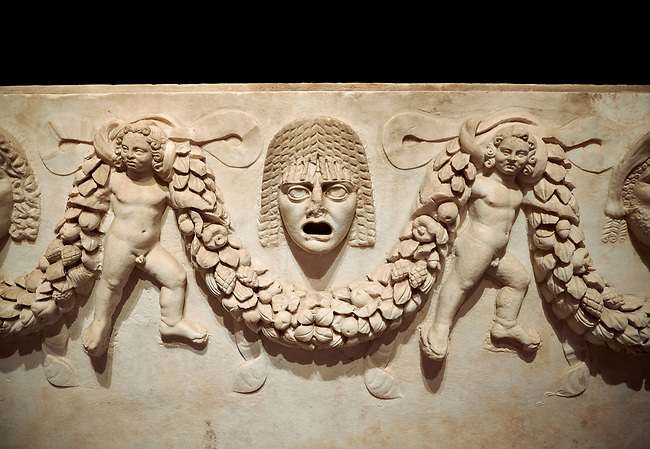 """Close up picture of Roman relief sculpted Sarcophagus of Garlands, 2nd century AD, Perge. This type of sarcophagus is described as a """"Pamphylia Type Sarcophagus"""". It is known that these sarcophagi garlanded tombs originated in Perge and manufactured in the sculptural workshops of Perge. Antalya Archaeology Museum, Turkey.  Against a black background."""