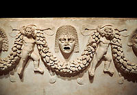 "Close up picture of Roman relief sculpted Sarcophagus of Garlands, 2nd century AD, Perge. This type of sarcophagus is described as a ""Pamphylia Type Sarcophagus"". It is known that these sarcophagi garlanded tombs originated in Perge and manufactured in the sculptural workshops of Perge. Antalya Archaeology Museum, Turkey.  Against a black background."