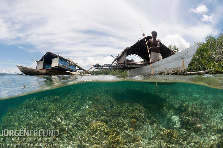 West Papuan fishermen in their outrigger house boat split level showing the shallow reef