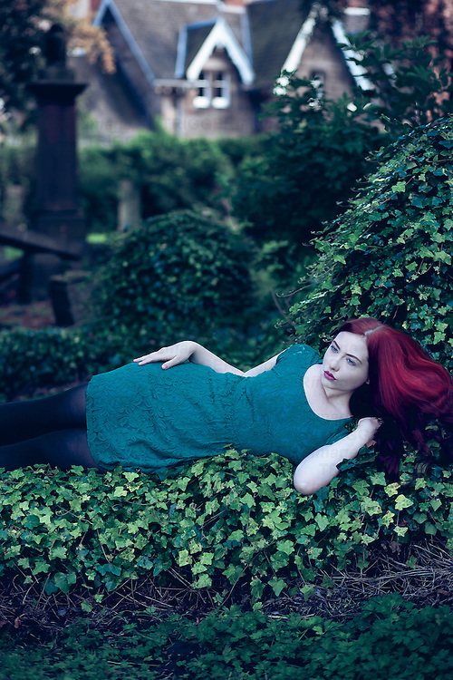 Young woman with long red hair wearing lace dress reclining on green ivy alone in graveyard