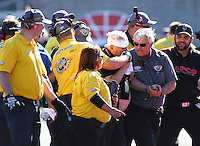 Oct 30, 2015; Las Vegas, NV, USA; NHRA safety safari personnel escort crew member Barry Paton to an ambulance after being hit by the car of NHRA top fuel driver Tim Boychuk during qualifying for the Toyota Nationals at The Strip at Las Vegas Motor Speedway. Mandatory Credit: Mark J. Rebilas-USA TODAY Sports