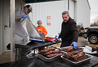 NWA Democrat-Gazette/CHARLIE KAIJO Ron Barnes of Bentonville (from left), Cooper Mayhew 10 of Bella Vista and Brent Mayhew of Bella Vista wrap racks of ribs in foil on Sunday, January 7, 2018 at the R.B.I. Baseball Academy of NWA in Bentonville. The academy is raising money to pay for entry fees, uniforms and other expenses for four of their age specific baseball teams: 10u, 11u, 12u and 14u. Their goal is to sell 1000 racks of ribs and raise $5000 for each team. Head Country Bar-B-Q prepared racks of ribs and chickens for the fundraiser. They will continue to sell racks of ribs until they run out.
