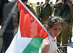 Israeli soldiers stand behind razor-wire and the Palestinian protesters girl hold Palestinian flag during a demonstration against the construction of Israel's separation barrier  in the West Bank village of Maasarah near Bethlehem, Friday,June 5, 2009. Photo Najeh Hashlamoun