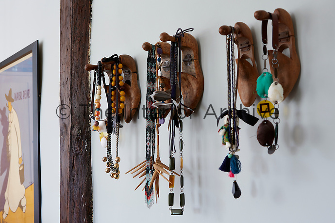 Vintage jewellery hangs from wooden shoes nailed on the wall.