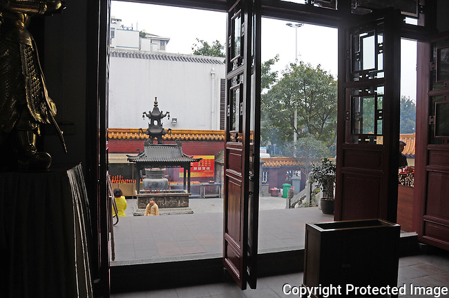 looking outside, through the open door panels of a Buddhist temple, at the large, ornate, incense burners in the courtyard, Guilin, China
