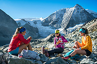 Three women trail runners taking a break to eat during the Via Valais, a multi-day trail running tour connecting Verbier with Zermatt, Switzerland.